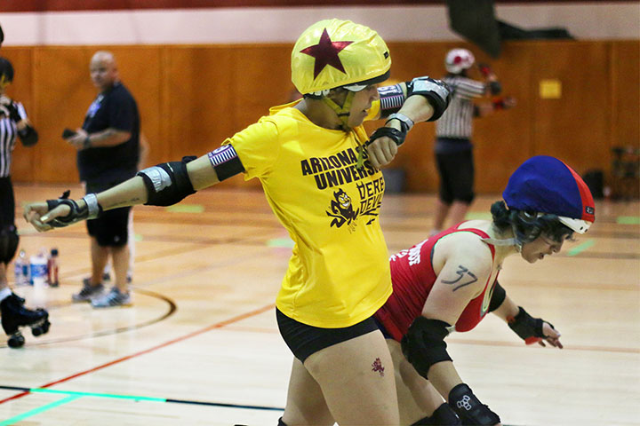 03222014 - Sigmund Droid (cq), 22, of the ASU Derby Devils blocks one of the UA Derby Cats during a match held in Mesa, Ariz. This was ASU's first roller derby match, albeit without a complete team. ASU beat the Derby Cats, 261-102.  Photo by Alec Damiano / JMC 351